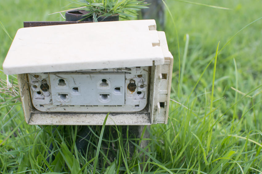 Close up Thai dirty electrical plug sockets are mounted in the plastic box stand with metal pole on the green grass garden in the park Box Green Plug Power STAND Electricity  Energy Garden Grass Metal Mount Outdoors Park Platic Pole Socket