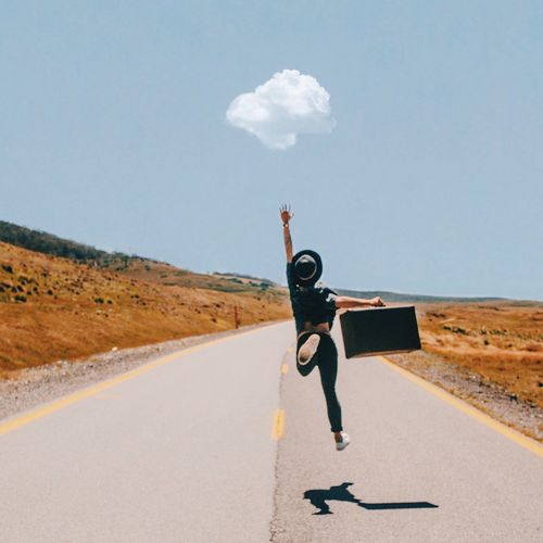 Full Length Rear View Of Woman Jumping While Holding Luggage On Road Against Sky
