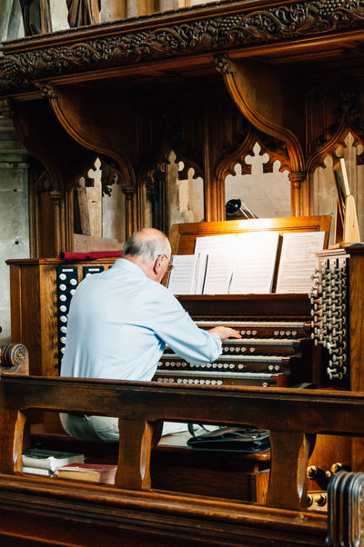 Man playing the organ in church Architectural Column Architecture Built Structure Cathedral Choir  Church Cirencester Column Culture Day Empty Man No People Organ Ornate Performance Place Of Worship Pray Religion Religious  Song Temple - Building Travel Destinations
