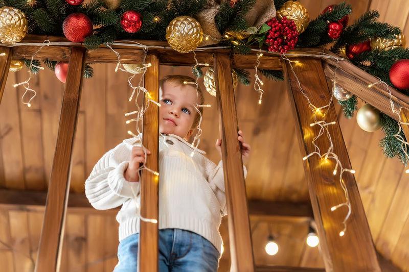 Full length of girl holding christmas decoration