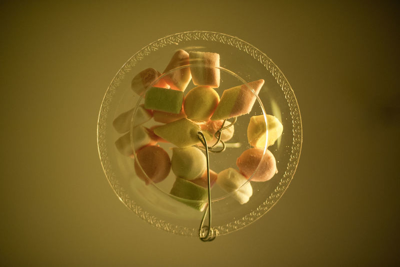 Variety of marsh mallows kept on transparent plate against colored background