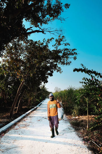 Rear view of couple walking on road amidst trees against sky