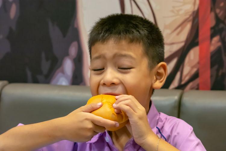 Close-up of boy eating burger
