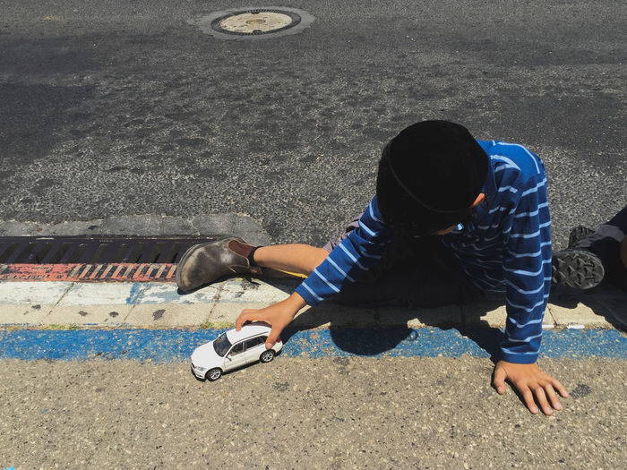 High angle view of boy playing with toy car on footpath
