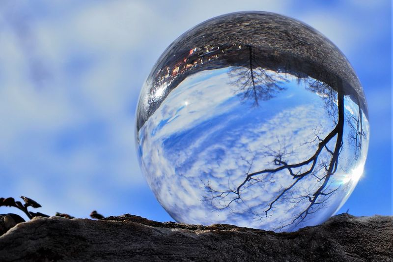 Close-up of crystal ball on rock against sky