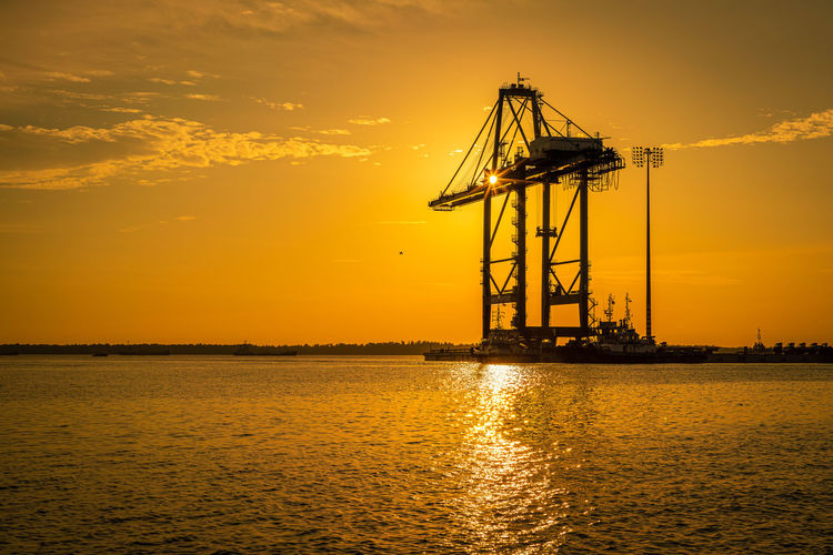 Silhouette crane by sea against sky during sunset