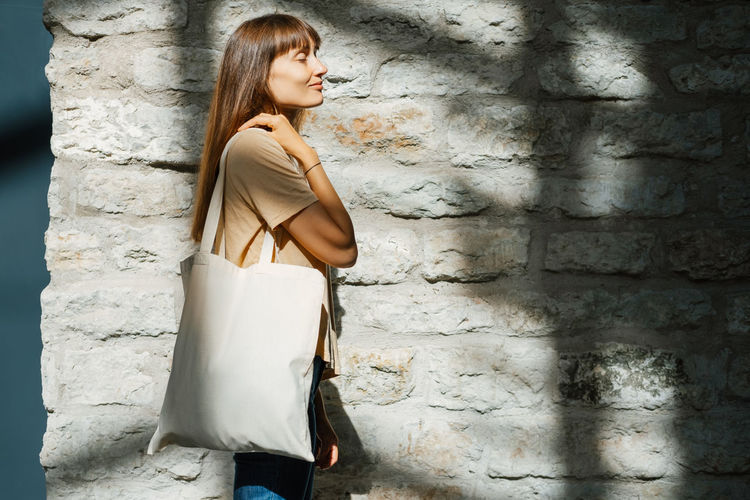 Woman holding white canvas tote bag. bag mockup for design.