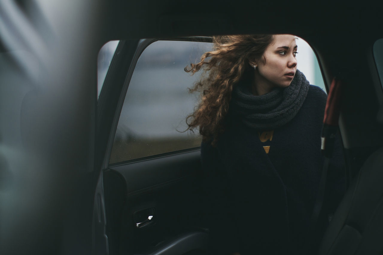 Beautiful woman wearing scarf standing at car door