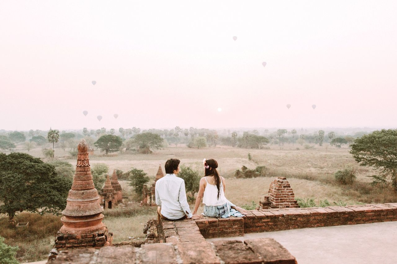 Rear View Of Couple Sitting On Temple Against Sky