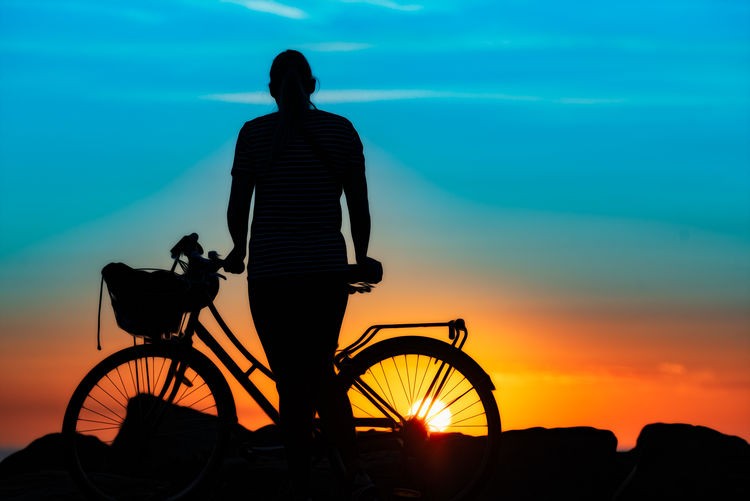 Rear view of silhouette man riding bicycle on sea during sunset