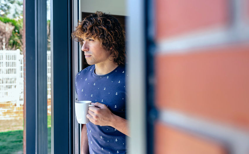 Man Having Coffee While Standing At Doorway