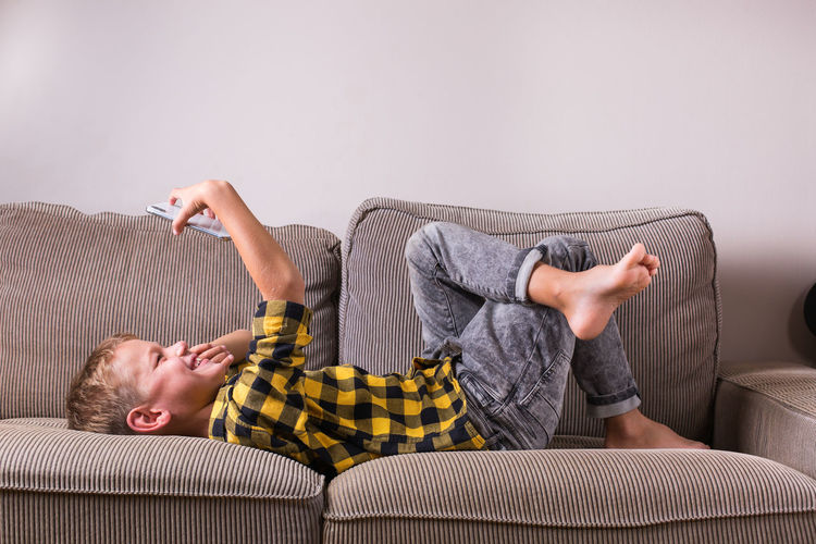 Midsection of man relaxing on sofa at home