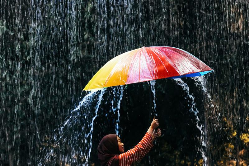 Side view of teenage girl holding umbrella in rain
