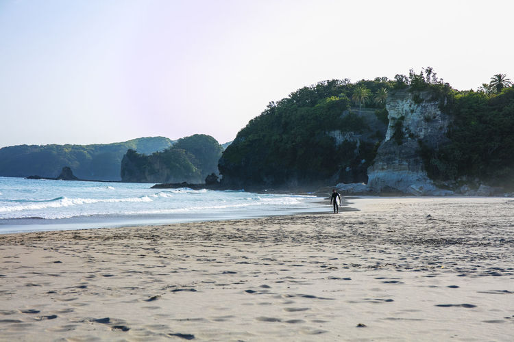 A surfer walking down the beach at Tatadohama Beach, outside of Tokyo. Sea Water Beach Land Sky Beauty In Nature Nature Day Wave Rock Surf Surfer Surfing Surfs Up Catching Rays Catching Waves Catching A Show Coast Coastal Japan Island Life Island Hang Ten Shred Board