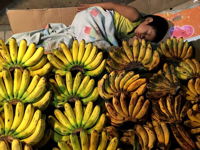 """A boy sleeps beside bananas his parents are selling on a sidewalk in Taguig, Metro Manila. When asked why is he not sleeping at home, the father replied """"there is nobody at home now. We need to sell our merchandise before we all go home together."""" (""""Walang tao sa bahay ngayon. Kailangan pa namin magtinda bago makauwi."""") Fruit Food One Person One Man Only Market Outdoors Banana Bananas Sleeping Child Boy Sidewalk Philippines Manila Taguig Fruits Food Stories"""