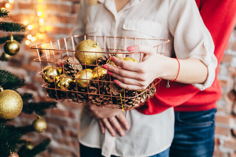 Midsection of couple holding container with christmas decorations at home