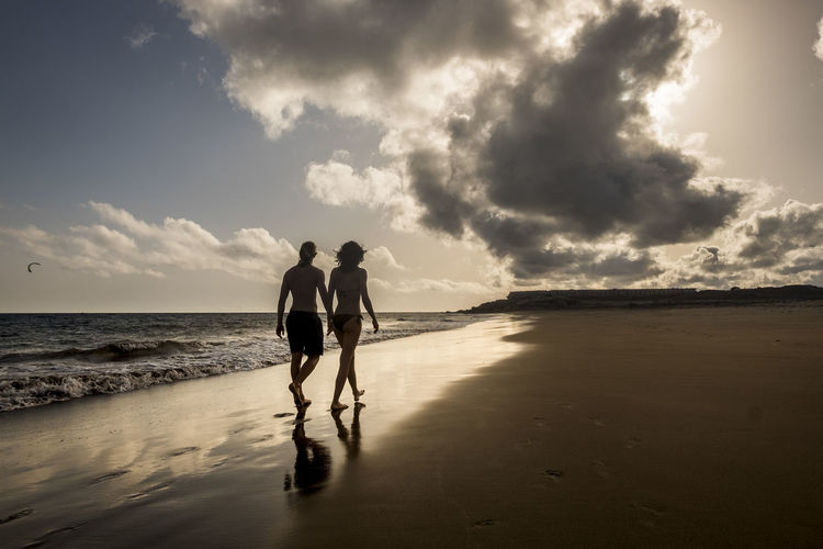 Rear View Of Man And Woman Holding Hands While Walking At The Beach During Sunset