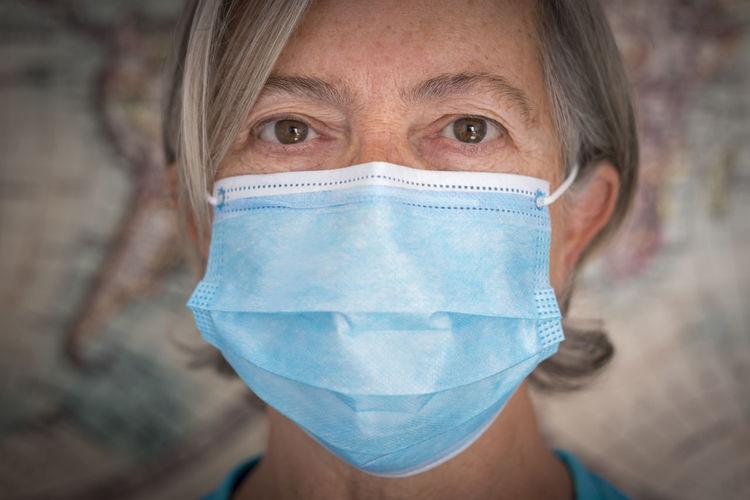 Close-up portrait of senior woman wearing flu mask