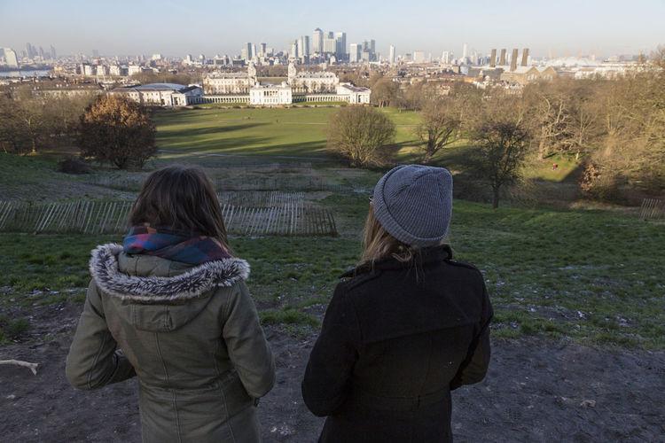 Rear View Of Female Friends Standing On Field