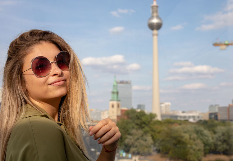 Portrait of smiling young woman against berliner fernsehturm