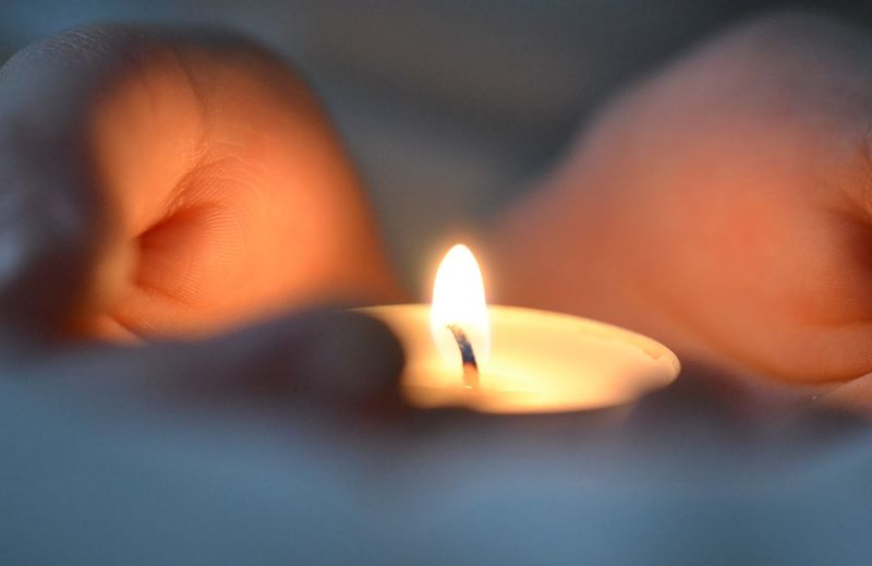 Close-up of hand holding lit candle