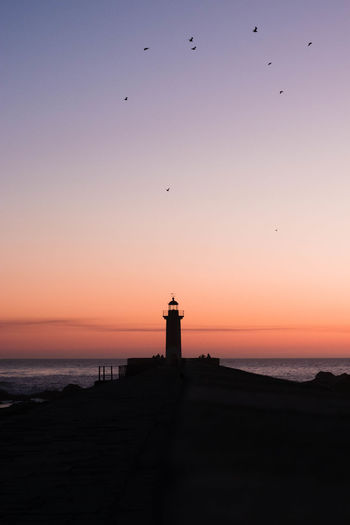 Silhouette of lighthouse against sky during sunset in porto
