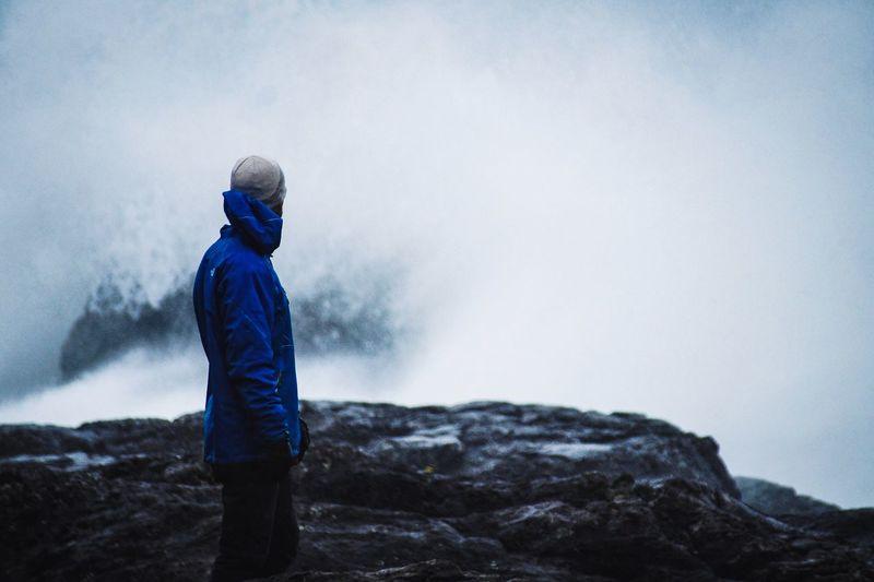Man standing on rock against ocean