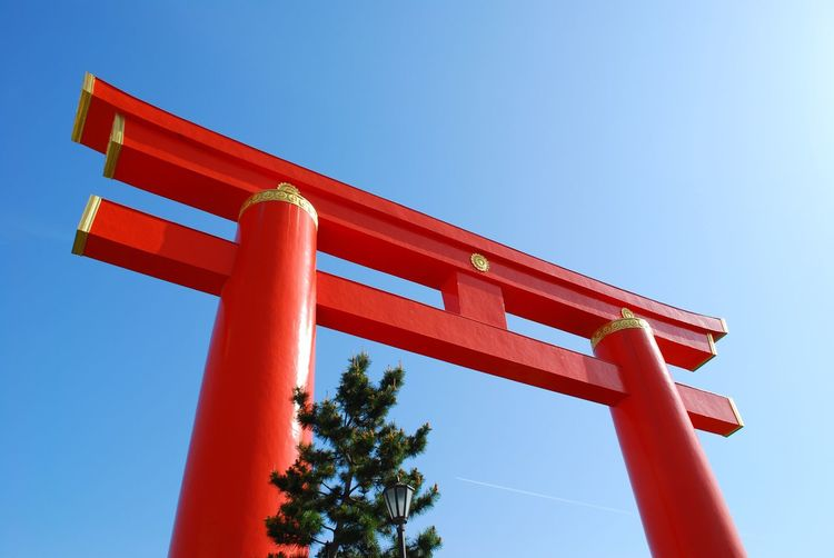 Low angle view of red wall against clear blue sky