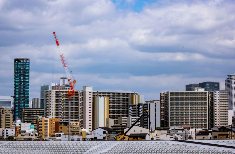 Construction site by buildings against sky