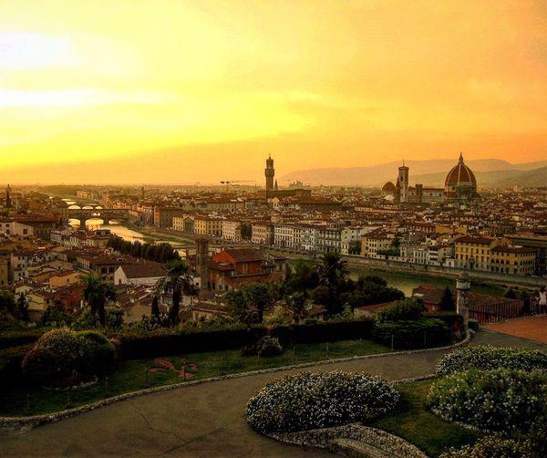 Duomo santa maria del fiore by arno river in cityscape against orange sky