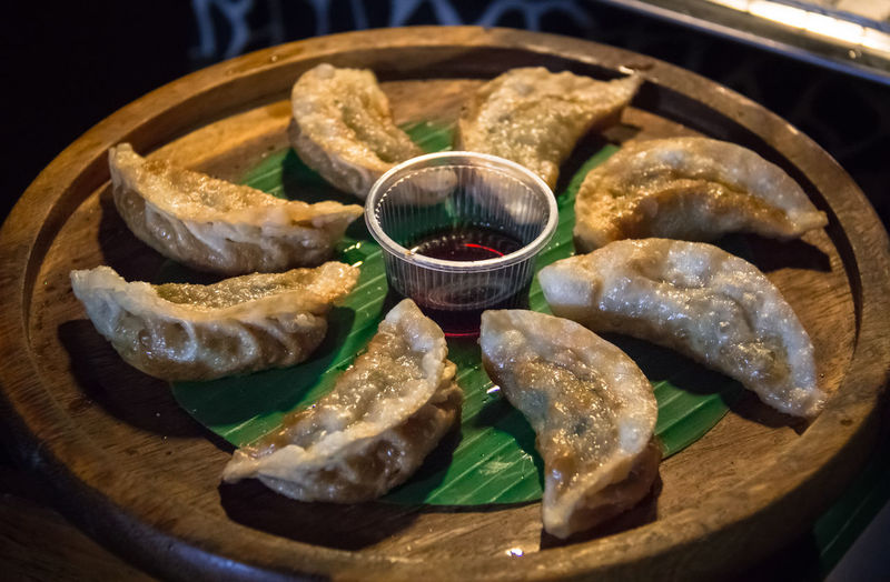 High angle view of hot deep fried gyoza served in the wooden plate with sauce