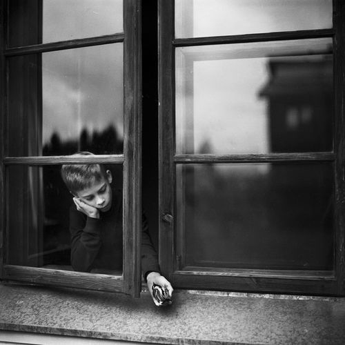 Portrait of boy looking through glass window