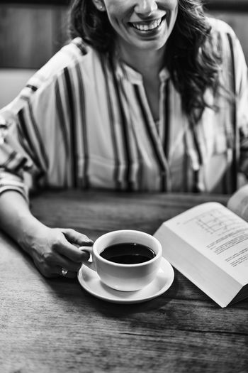 Woman Drinking Coffee and Reading Book Coffee Female Kettle Woman Cafe Home Drink Young Girl Cup Hot Glass One Person Enjoy People Caucasian Happy Lifestyles Drinking Coffee Concept Caffeine Indoors  Holding Beautiful Adult Casual Break Table Aroma Close Up Drinking Happiness Coffee Cup Relaxation Black And White Mug Coffee - Drink Indoors  Smiling Front View Sitting