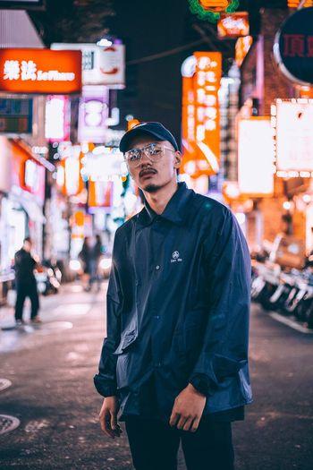 Man standing on city street at night