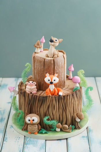 Enchanted forest woodland themed fondant cake with a hedgehog, deer, owl, fox, snail, tree trunk, ferns, mushrooms and leaves on wooden background Birthday Cake Deer Fondant Cake Tree Tree Trunk WoodLand Animal Cake Celebration Character Fern Figurine  Fondant  Food Food And Drink Forest Fox Guitar Kid Mushroom Owl Still Life Sugar Arts Sweet Food Theme