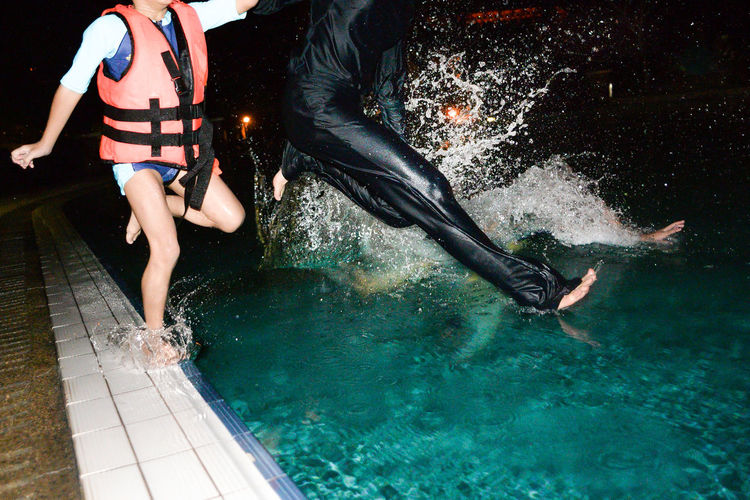Friends jumping in swimming pool at night