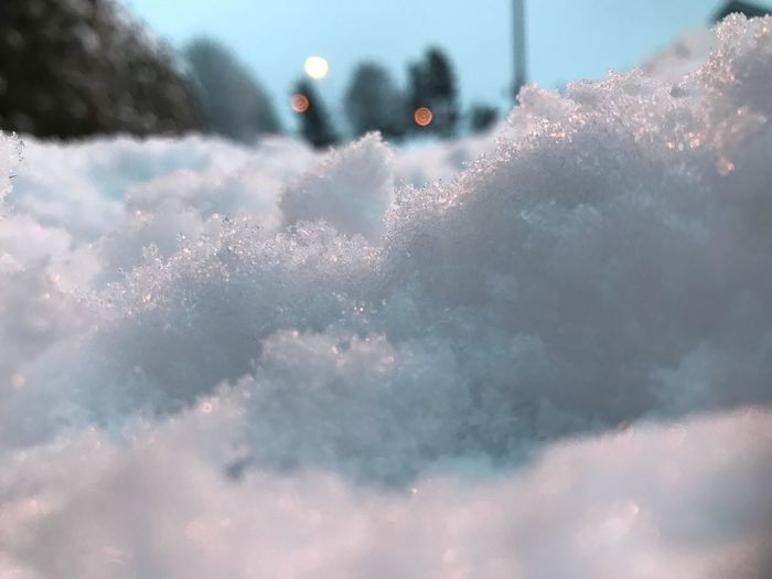 Close-up of snow in city against sky