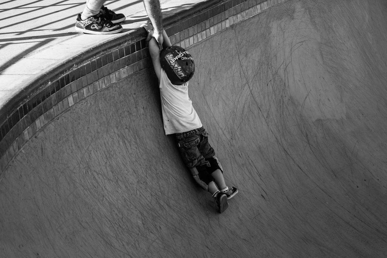 full length, childhood, high angle view, one person, casual clothing, leisure activity, real people, boys, day, risk, skateboard park, outdoors, lifestyles, playing, low section, child, one boy only, people, adult