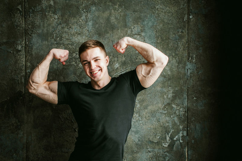 Close-Up Portrait Of Muscular Man Flexing Muscles By Wall