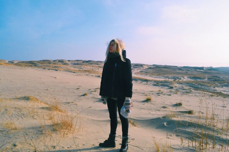 Full length of thoughtful woman standing on sandy landscape against sky