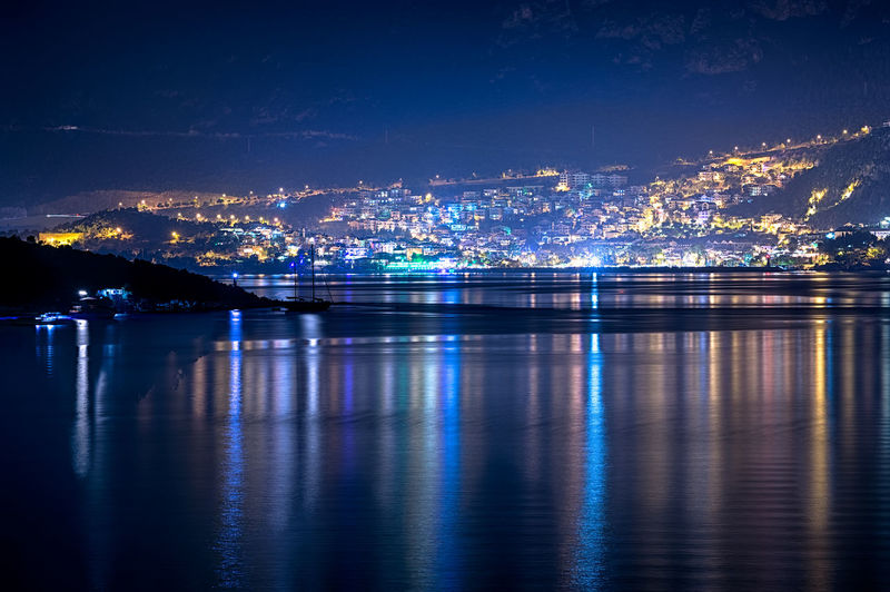 View Of Illuminated Community On Mountain By River At Night