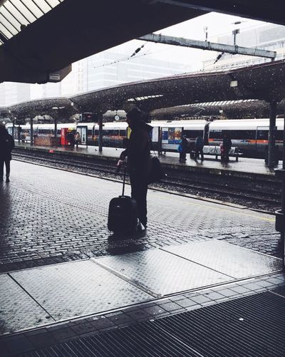 Person standing with suitcase at railroad station platform