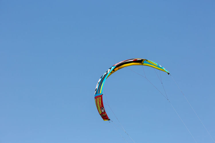 Low angle view of kite flying against clear blue sky