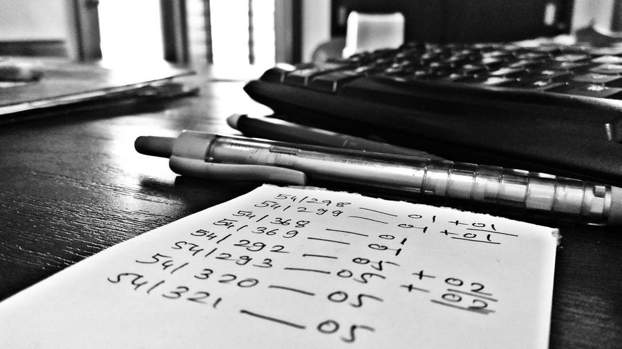 Close-Up Of Pens And Note Pad On Table In Office