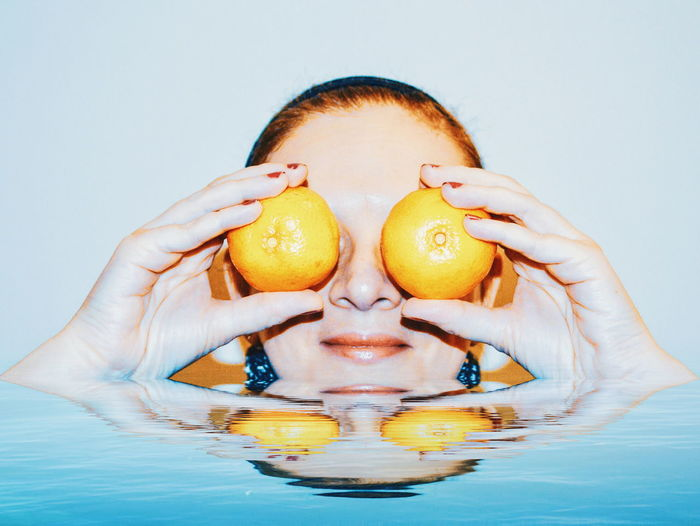Woman covering eyes with fruits in bathtub