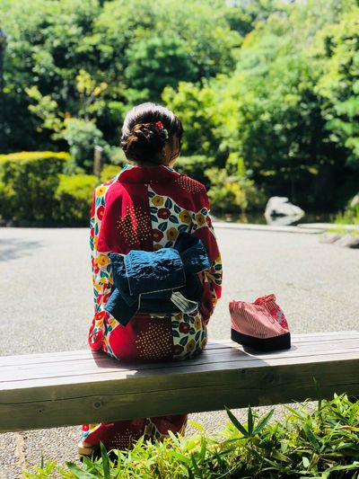 Rear View Of Woman In Kimono Sitting On Bench
