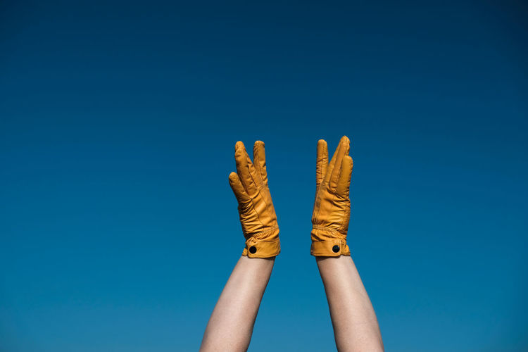 Cropped hands of woman wearing gloves against blue sky