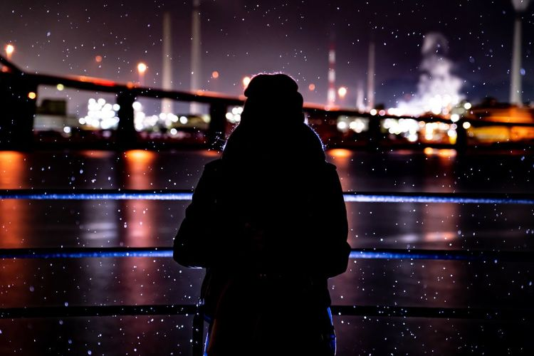 Rear view of silhouette woman standing in illuminated city during snowfall