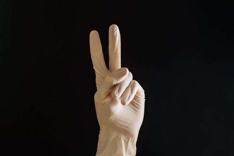 Close-up of hand showing peace sign against black background