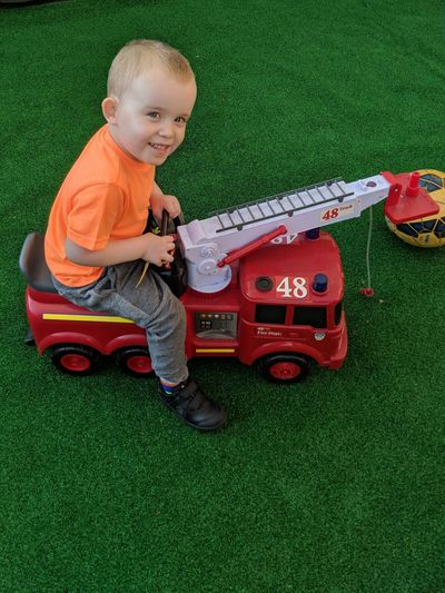 High angle portrait of cute boy playing with toy fire engine on turf